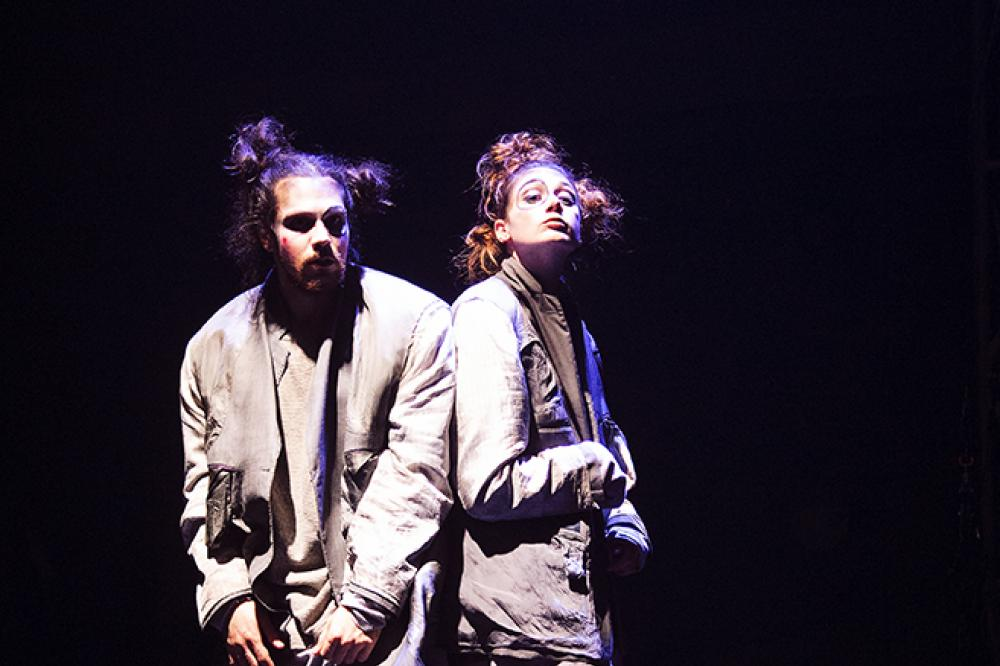 Two performers in loose fitting gray suits and messy space buns stand back to back. One looks off to the side while the other looks down their nose at the camera. They both have quizzical looks on their faces. They are under stage lights and the background is black.