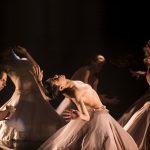 Focus Cia de Dança, ímpar, Photo by PAULA KOSSATZ: Five dancers in blush circle skirts are on a black stage. The lighting is low and they are all arching back or bending forward. They are all bare-chested.