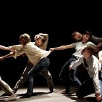 Alan Lake Factorie, Le Cri Meduses: Eight dancers in jeans and light-coloured shirts are spread out across the screen pulling each other and being pulled. They are in a spotlight and the background is black.