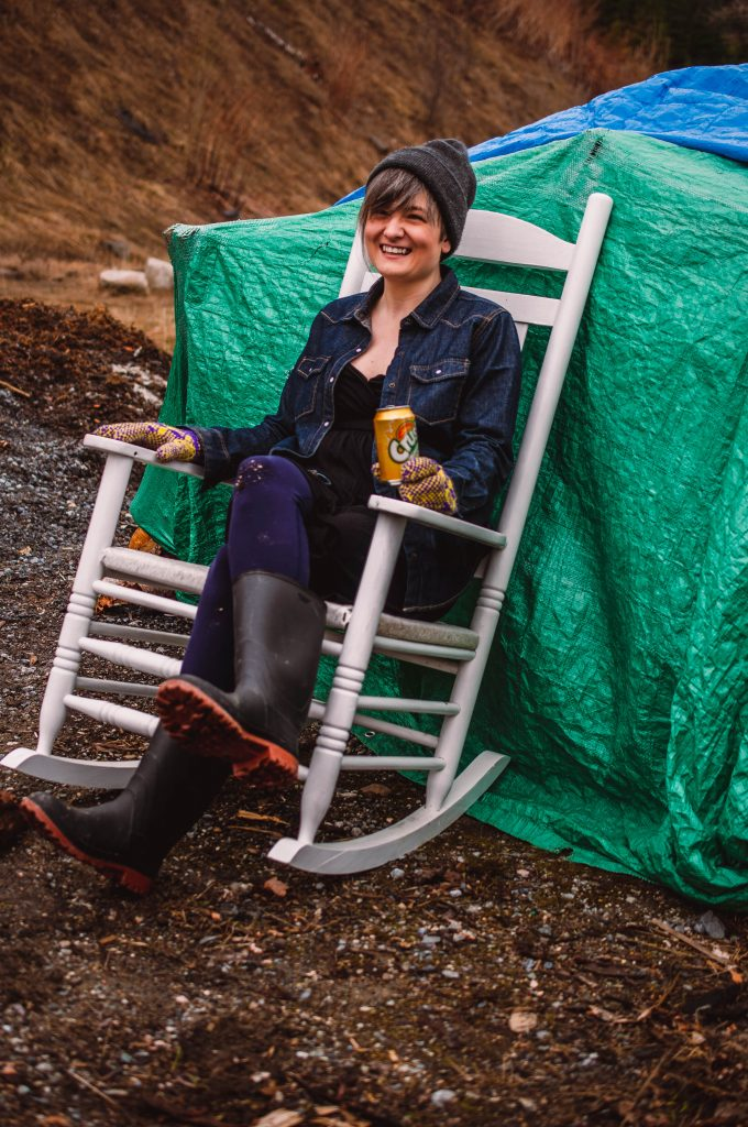 Candice Pike is a white woman with a round face and a big smile. She is wearing a grey toque, jean jacket and sits on a white wood chair in front of a green tarp. She is outside and holding a can of pineapple Crush.