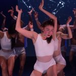 Red Sky Performance: A group of people in white leotards and shorts with mesh around their waists. They are all squatting holding their arms above their head that are bent at the elbow and wrist. They have white body paint on their eyes and thighs.