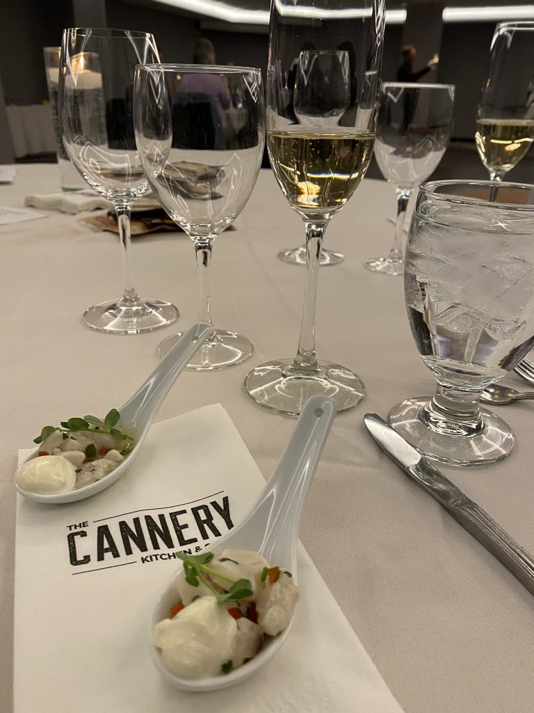 """Live Art Dance Wine Tasting Fundraiser: Empty glasses sit on a white table cloth. Two canapes in spoons are on the table, and a napkin that reads """"The Cannery Kitchen & Bar"""""""
