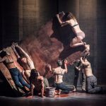 Alan Lake Factorie, Le Cri Meduses: Seven dancers in various states of undress either support or hang off of a wooden L-shaped set piece that is tilting at a 45-degree angle. There is a bucket and fake blood on the floor and on eth dancers.