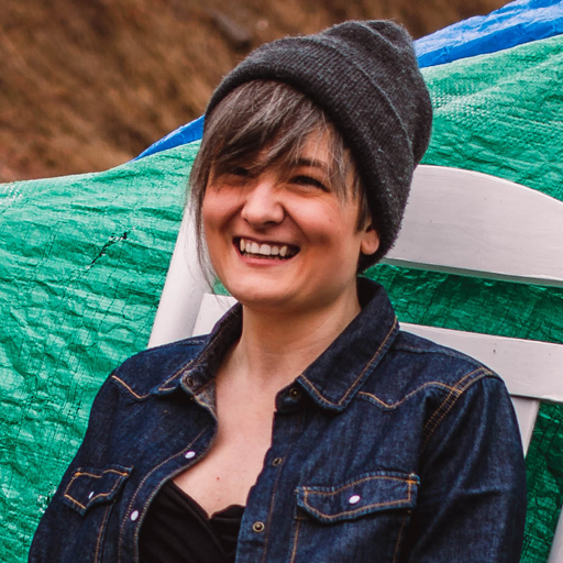 Candice Pike is a white woman with a round face and a big smile. She is wearing a grey toque, jean jacket and sits on a white wood chair in front of a green tarp.