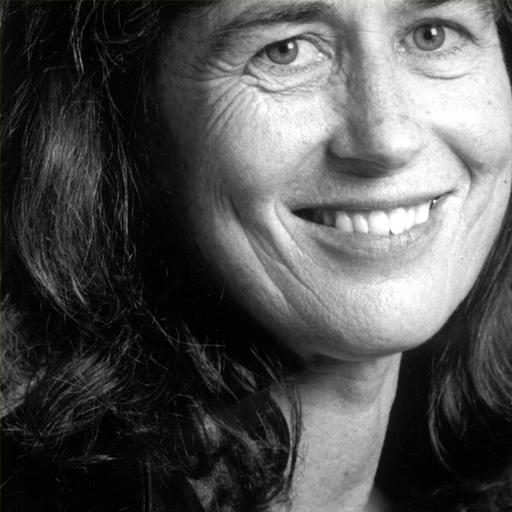 Diane Moore: This photo is in black and white. She is a white woman with dark, long wavy hair, she has brown eyes and is smiling into the camera.