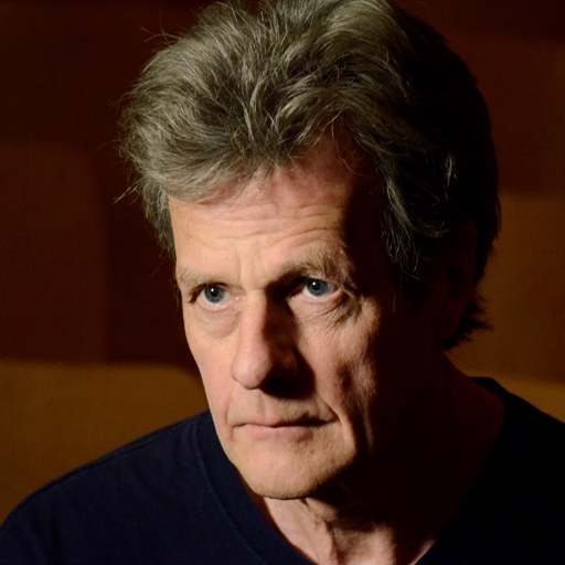 Randy Glynn, a middle-aged white man with dark grey hair and blue eyes. He looks slightly off camera with a focused stare. He wears a navy crew neck and the background is chocolate brown.