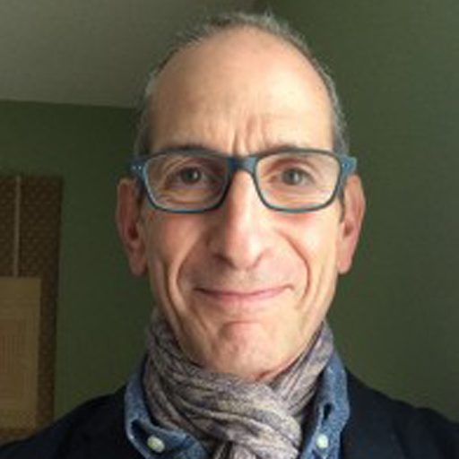 Seth Levinson is a middle-aged white man with blue glasses and very short gray hair. He is looking into the camera with a warm smile. He has a pale purple scarf and black sweater on. The room he is in is pale green.