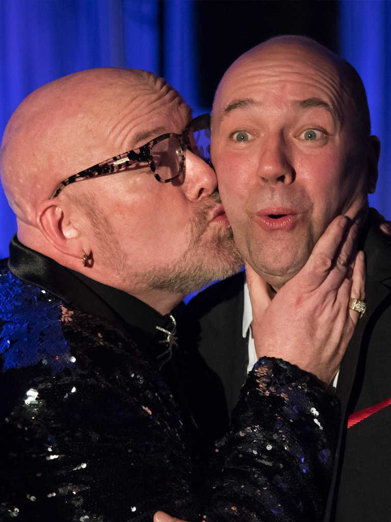 Twisted Black Tie Fundraiser, the host of the event kisses politician Andy Filmore on the cheek who is making a surprised face. They are both bald white men wearing black formal wear.