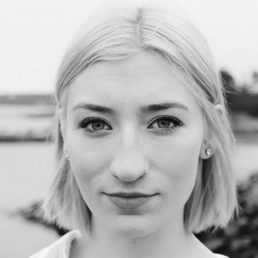 Anastasia Wiebe is a white woman with short platinum blonde hair that goes to her chin. She has darker eyebrows, a nose ring and eyeliner on. She stands outdoors and the photo is black and white.