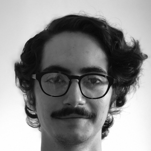 Jay Harvey has dark, thick frame glasses. He has short, darky curly hair with a side part and a thin moustache. He looks directly into the camera with a slight smile.