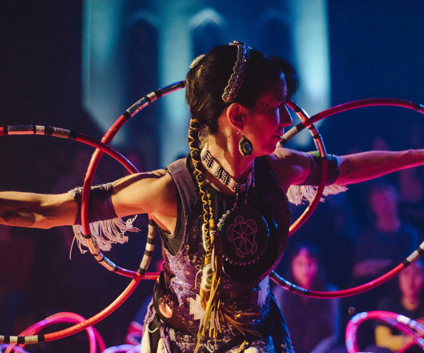 A'NÓ:WARA DANCE THEATRE, Sky Dancers: Bridges - Barbara Diabo, an Indigenous woman dressed in a traditional costume looks to the side with hoops along her back.